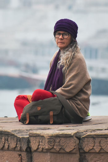 Portrait of woman sitting by sea during winter