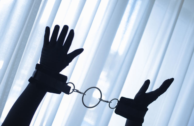 Cropped hands of silhouette person with handcuffs against window