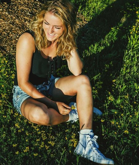 High angle view of happy young woman sitting on grassy field