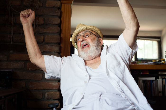 happy old man Arms Raised Beard Caucasian Chair Comfortable Day Elderly Eyeglasses  Front View Hat Indoors  Lifestyles Man Old One Person Pensioner People Real People Relaxing Rest Resting Retirement Senior Adult Sitting White