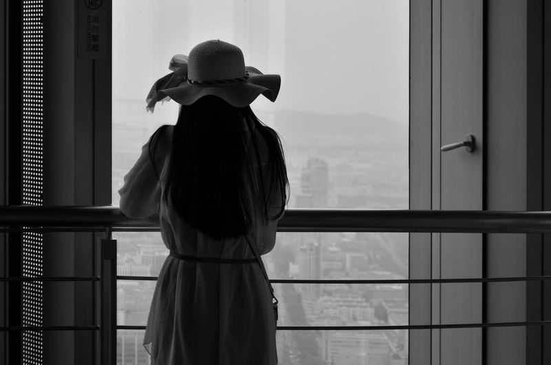 Rear view of woman standing against window