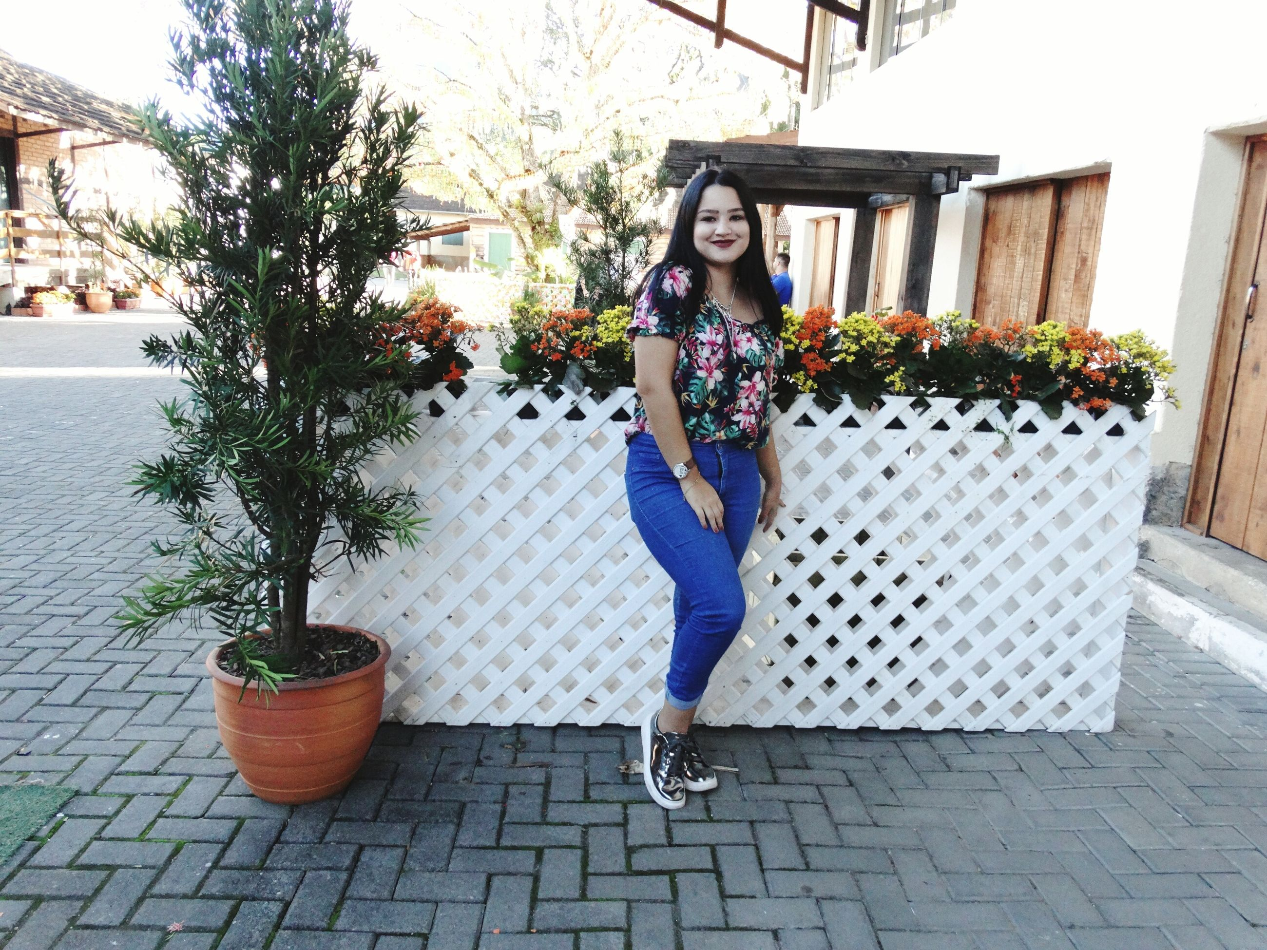 full length, one person, young adult, potted plant, outdoors, young women, beautiful woman, smiling, plant, looking at camera, front view, flower, day, portrait, real people, lifestyles, standing, growth, posing, architecture, tree, adult, people