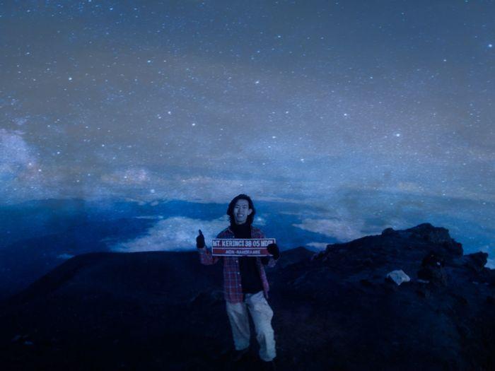 Full length of man sitting on rock at night