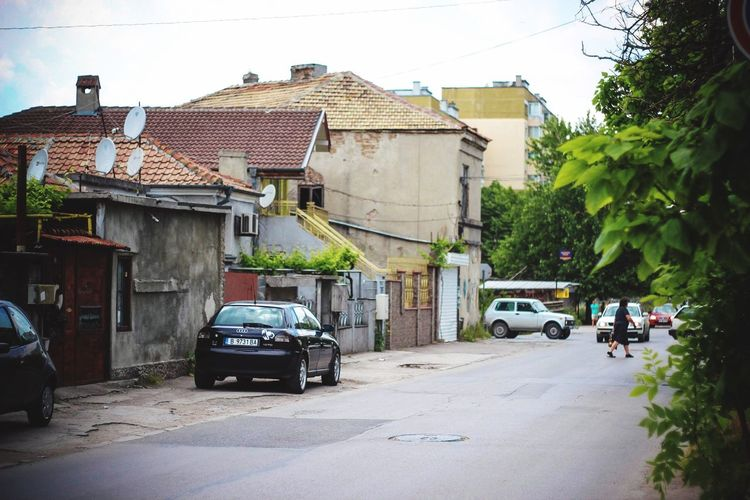 Cars on road against houses in city
