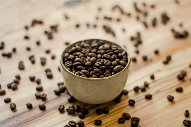 Food And Drink Freshness Food Wood - Material Roasted Coffee Bean Large Group Of Objects Table Indoors  Still Life Brown No People High Angle View Coffee - Drink Close-up Coffee Abundance Focus On Foreground Seed Selective Focus Wellbeing Caffeine