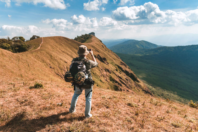 Full length rear view of hiker on mountain against sky