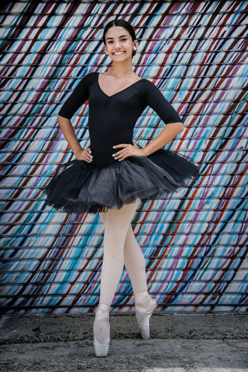 Portrait of happy ballerina against patterned wall