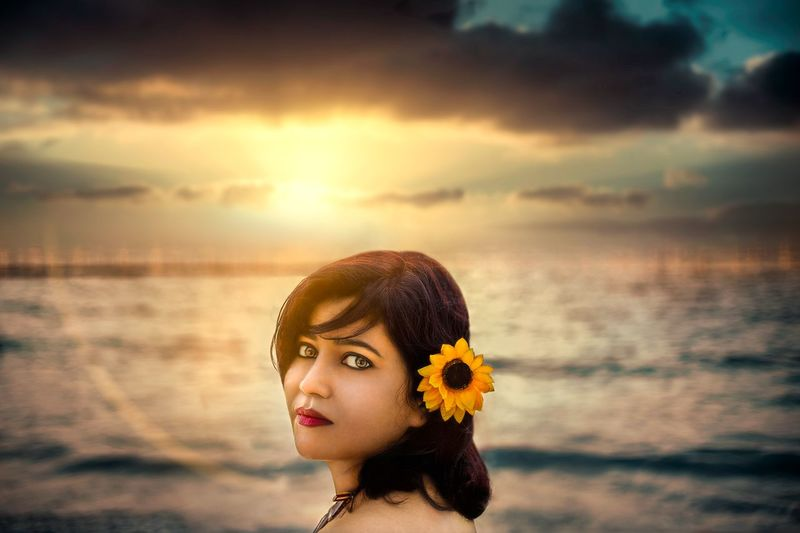 Portrait of woman against sea during sunset