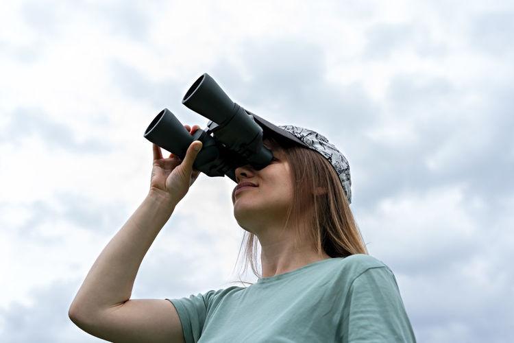 Young blonde woman bird watcher looking through binoculars at cloudy sky ornithological research