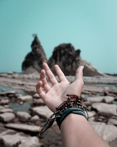 Low section of person hand against clear sky