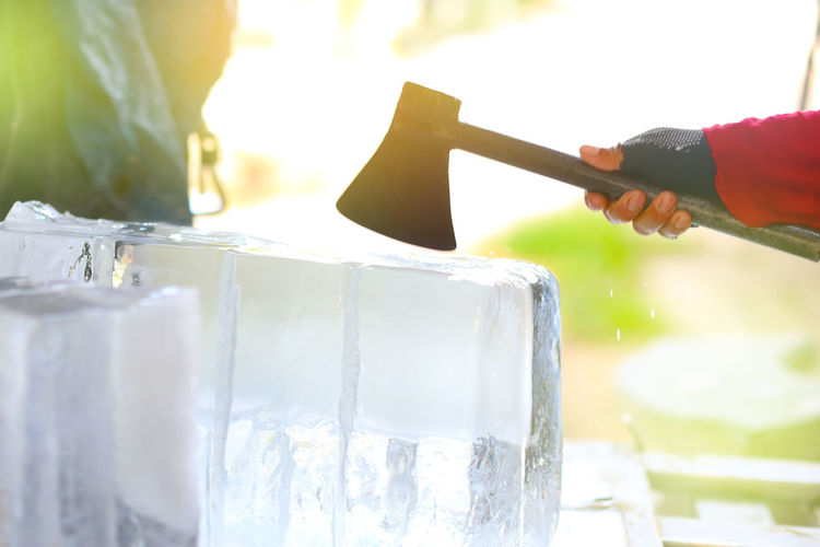 Cropped hand breaking ice with axe