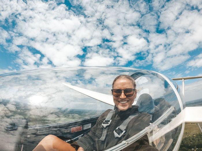 Flying high Smiling Portrait One Person Transportation Cloud - Sky Mode Of Transportation Adult Sky Day Travel Selfie Adventure Flying Piloting Glider Courage New Beginnings Hobby Female Pilot Girl Power Women Doing What Was Traditionally Mens Work Female Seatbelt