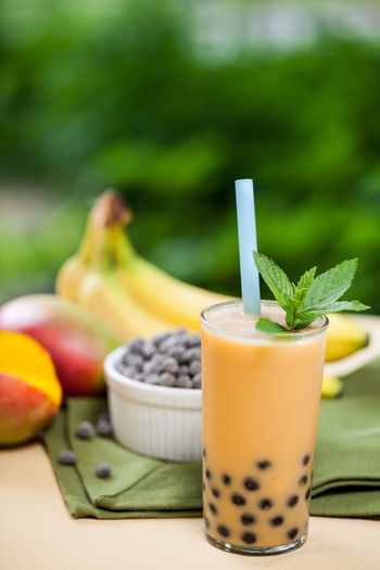 Mango smoothie bubble tea with fresh mango and bananas in the garden Beverage Bubble Tea Mango Bananas Day Drink Focus On Foreground Food And Drink Freshness Fruit Fruit Drink Garden Green Color Healthy Eating Mango Smoothie Mint Leaves No People Outdoors Refreshing Smoothie Straw Table Tapioca