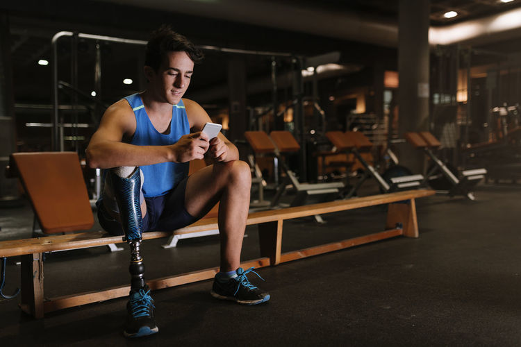 Full length of young man with prosthetic leg using phone while sitting on bench in gym