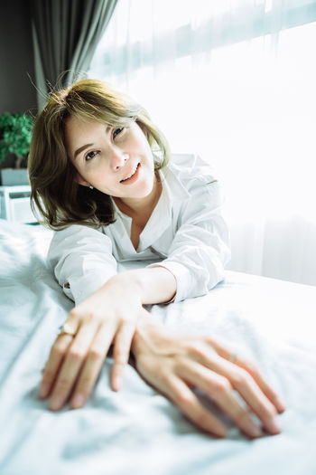 Portrait Of Smiling Young Woman On Bed At Home