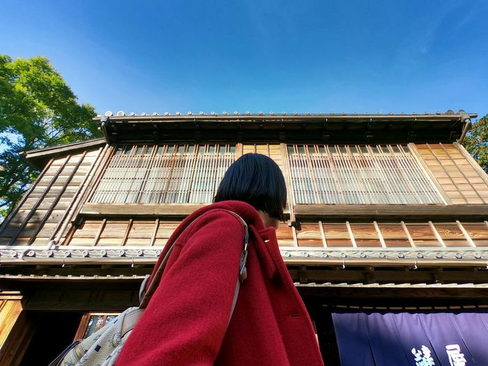 Rear view of woman against building against clear blue sky