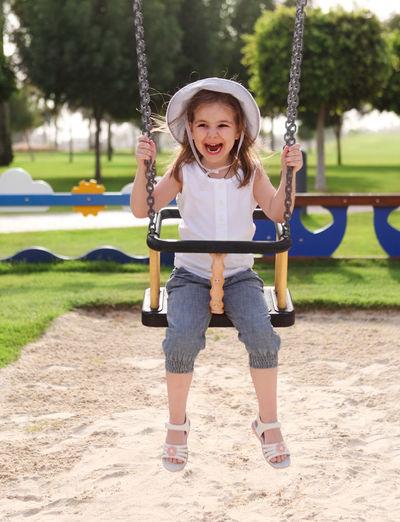 Full length of girl on swing in park