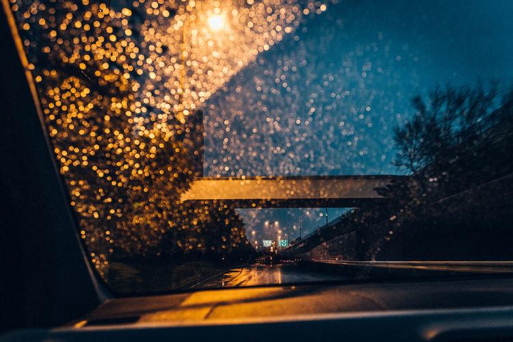 Illuminated road seen through car window