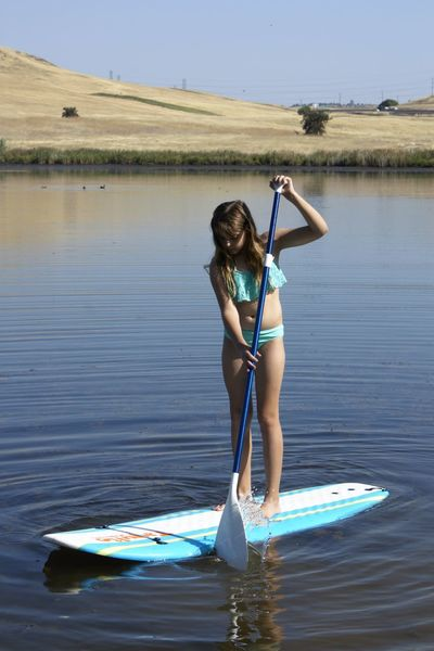 Girl learning to paddleboard on a calm lake Adventure Aquatic Sport Balance Beach Full Length Lake New Challenge One Girl Only Outdoors Paddleboarding Summer Tranquility Water Watersports