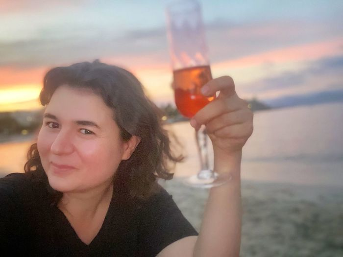 Portrait of young woman drinking glass against sea at sunset