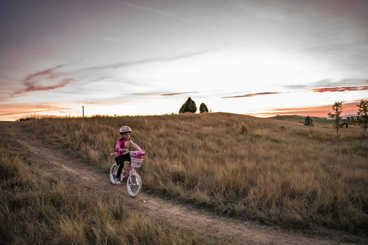 Woman riding motorcycle on field against sky during sunset