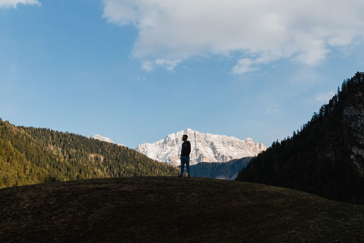 Man Standing On Hill Amidst Mountains Against Sky