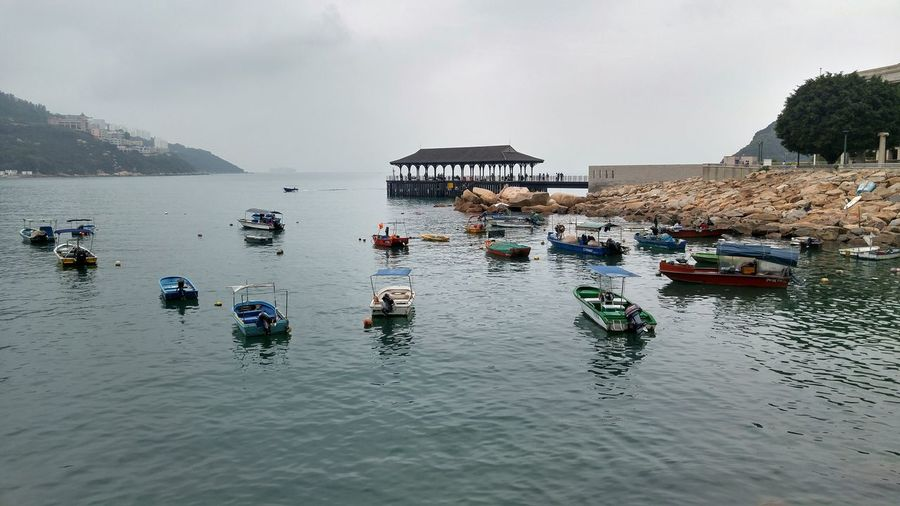 Walking along the coast of Stanley Hong-Kong Boats Waves, Ocean, Nature Boats And Water Beautifulphoto with Dusk Like Sky expressing the Dockside Landscape