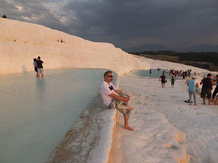 People at travertine pool against sky