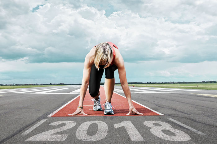 Female runner waits for his start at an airport runway. In the foreground the painted date 2018. 2018 Date Text Adult Cloud - Sky Day Full Length Lifestyles One Person Outdoors People Road Running Track Sky Sport Sports Clothing Sports Race Sports Track Starting Line Symbol Women Year Young Adult Young Women