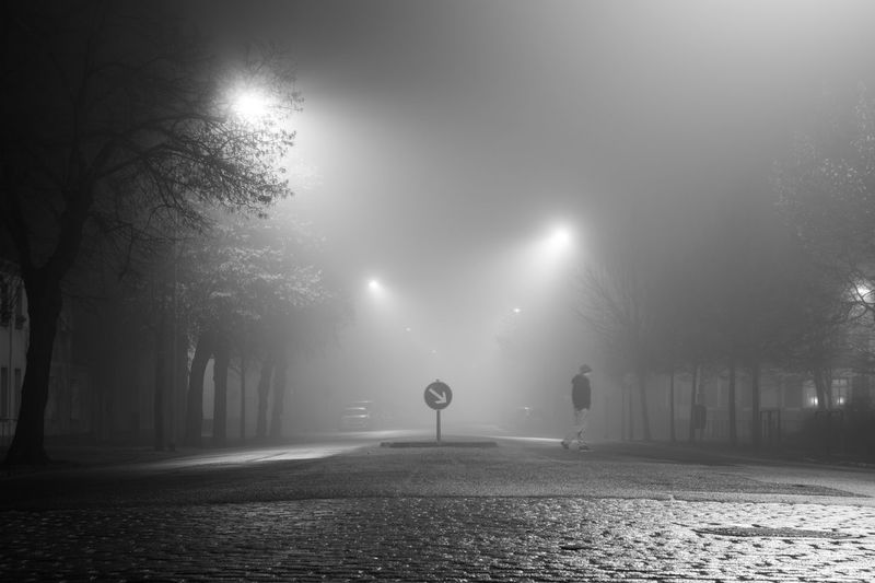 Full length of man walking on illuminated cobbled street at night during foggy weather