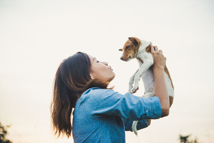 Low angle view of woman holding puppy against clear sky