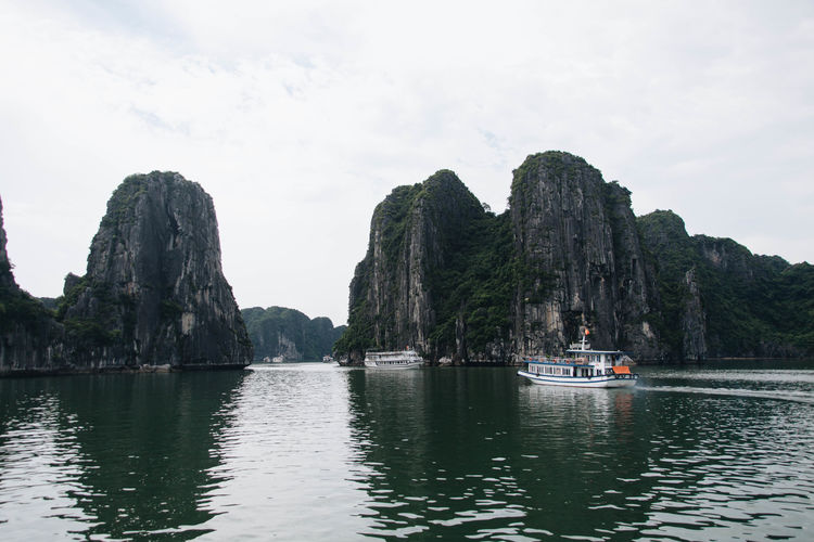 Halong Bay Vietnam Vietnam Beauty In Nature Cliff Day Longtail Boat Men Mountain Nature Nautical Vessel One Person Outdoors People Physical Geography Real People Rock - Object Rock Formation Rocky Mountains Scenics Sea Sky Tranquility Transportation Water