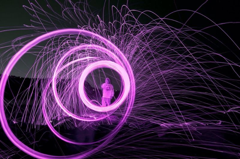 Man spinning illuminated wool at night