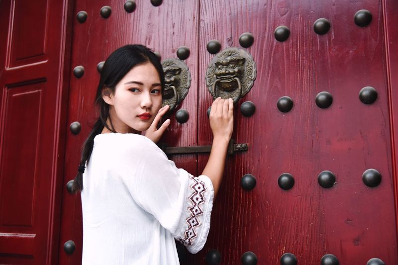 Young woman holding door knockers of maroon wooden gate