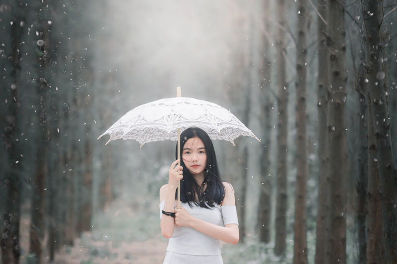 Portrait Of Beautiful Young Woman Holding Umbrella During Winter