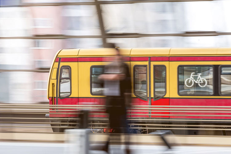 Blurred motion of person and train at railroad station platform