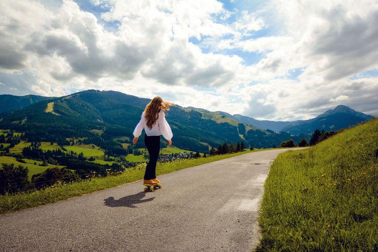 Full length of woman skateboarding on road against sky