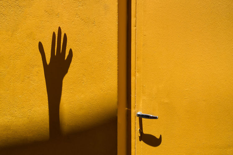 Shadow Of Person Hand By Yellow Door