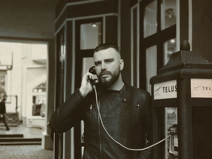 Portrait of mid adult man calling through telephone booth
