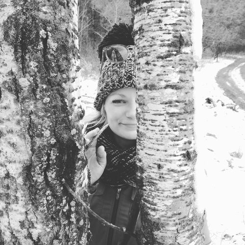 Portrait Of Smiling Woman Standing By Tree In Forest