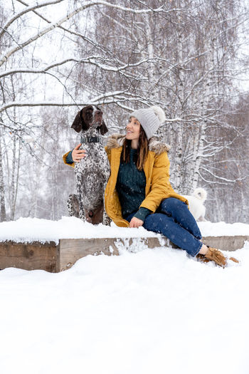 Yellow Stylish Lifestyle Snow Winter Cold Temperature Warm Clothing Outdoors Tree Women Adult Nature Hat Two People Clothing Full Length Togetherness Happiness Glove Sitting Females Heterosexual Couple Positive Emotion Couple - Relationship Snowing Scarf