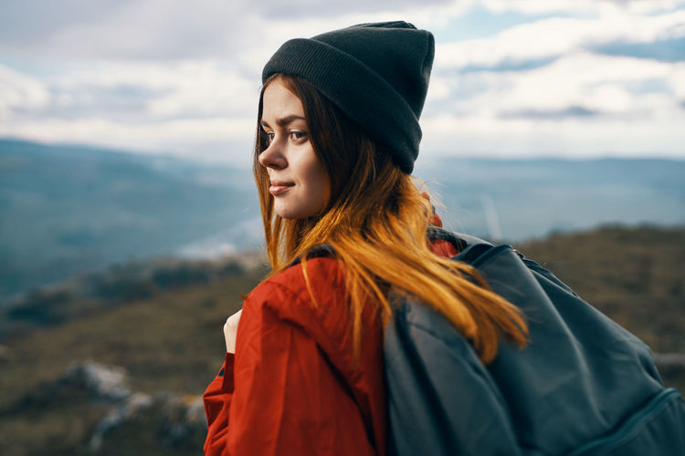 Beautiful young woman looking at mountains against sky