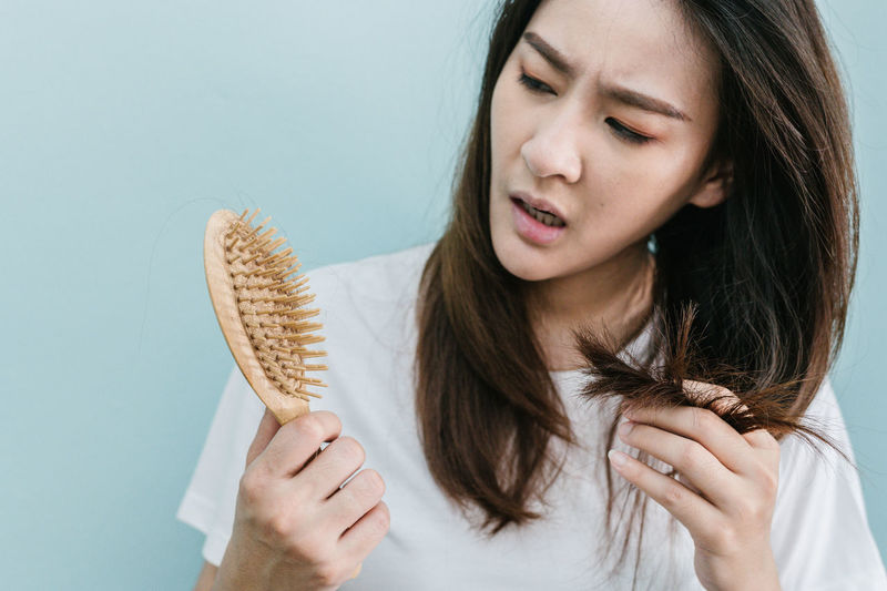 Worried woman holding brush with hair against blue background
