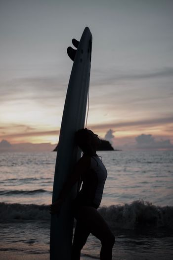 Low angle view of silhouette person on beach against sky during sunset