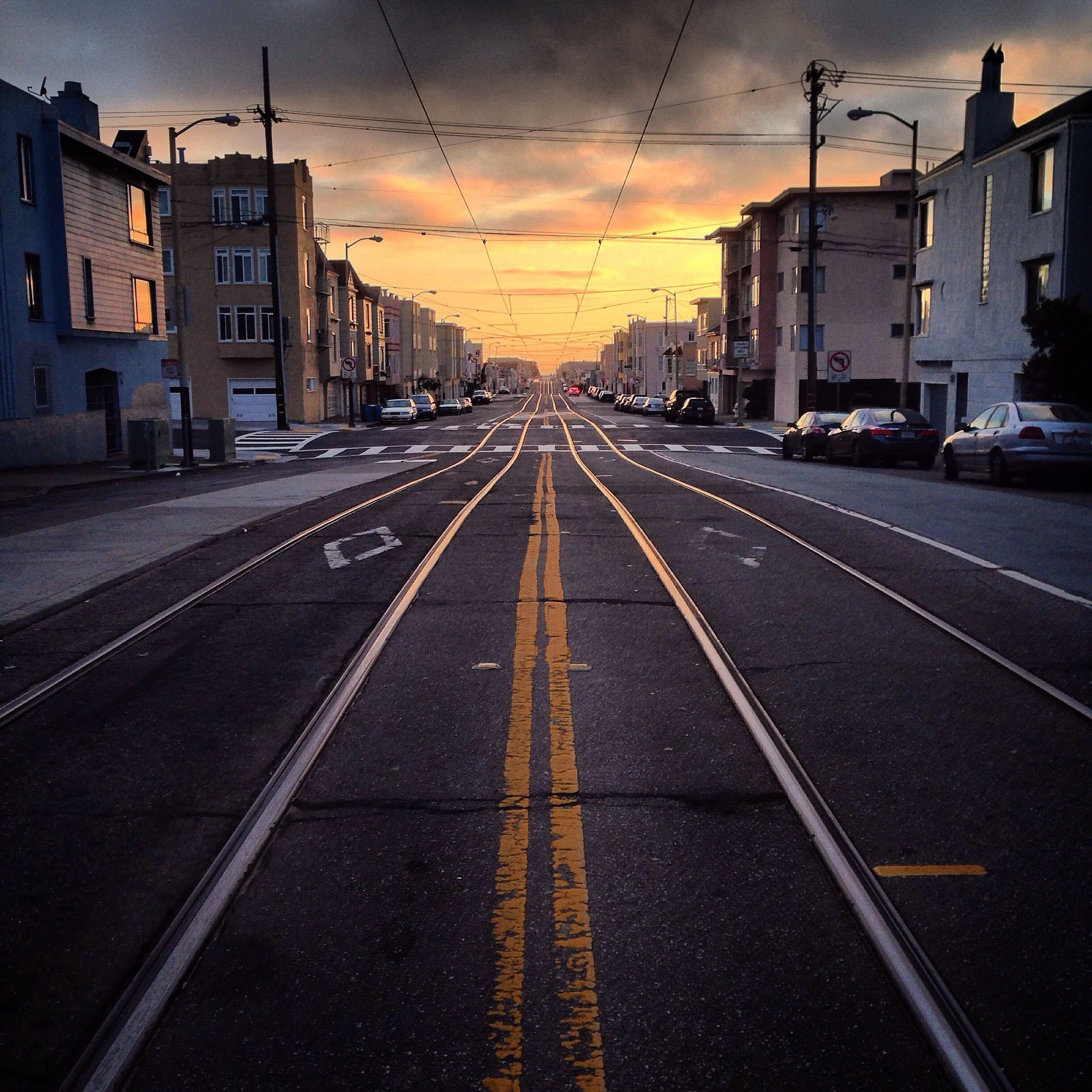 building exterior, transportation, the way forward, architecture, built structure, diminishing perspective, city, sunset, road marking, vanishing point, street, sky, road, asphalt, city life, railroad track, surface level, tramway, outdoors, dusk
