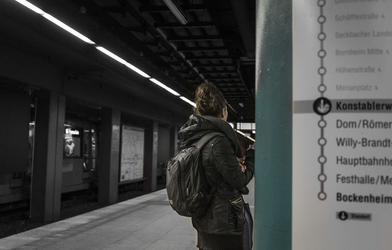 Rear view of man standing by text in city