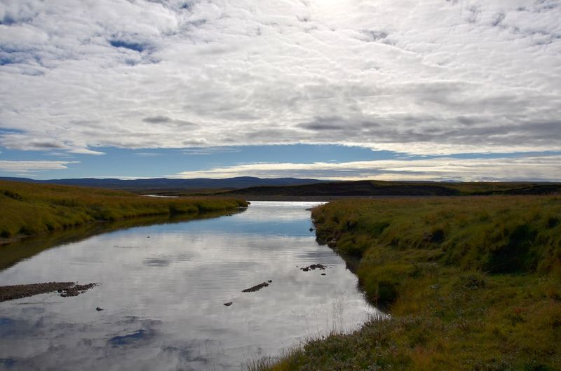 Grassland in southern IcelandLandscape Reflection Water Scenics Cloud - Sky Outdoors Mountain Tranquility Beauty In Nature Nature No People Sky Day River Grassland Southern Iceland Iceland Nature Tourism