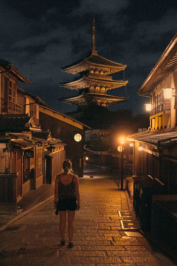 Rear view of woman walking on illuminated street amidst buildings at night