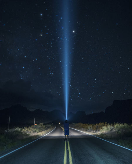 Rear view of man holding flashlight against sky at night