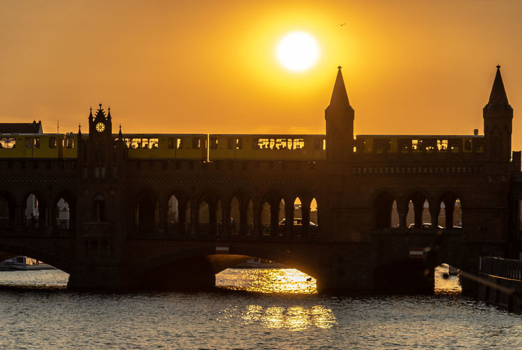 Arch bridge over river during sunset
